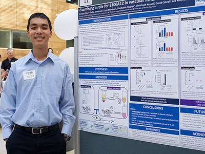 Jordan standing next to his research poster